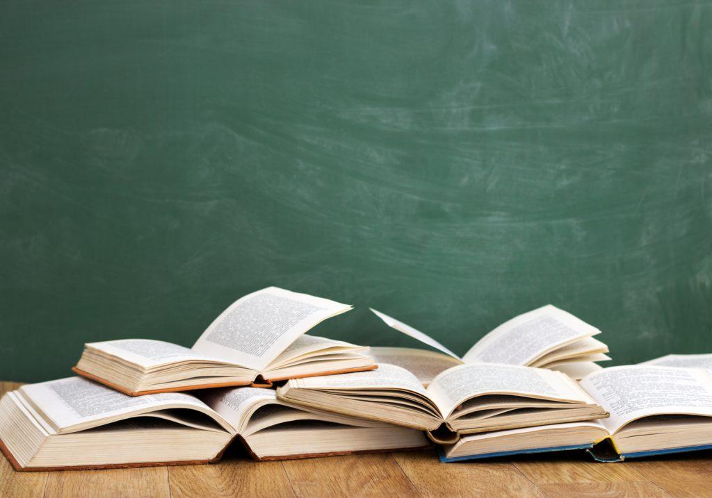 Aufgeschlagene Bücher vor Tafel