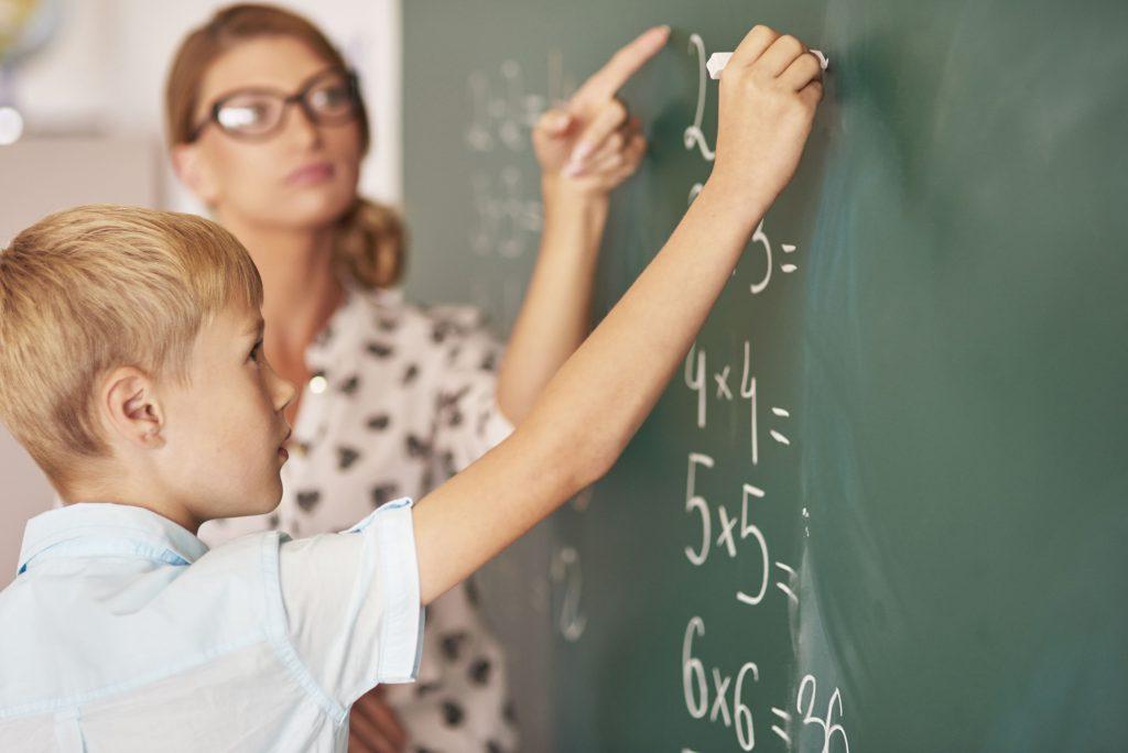 Schüler und Lehrerin vor Schultafel