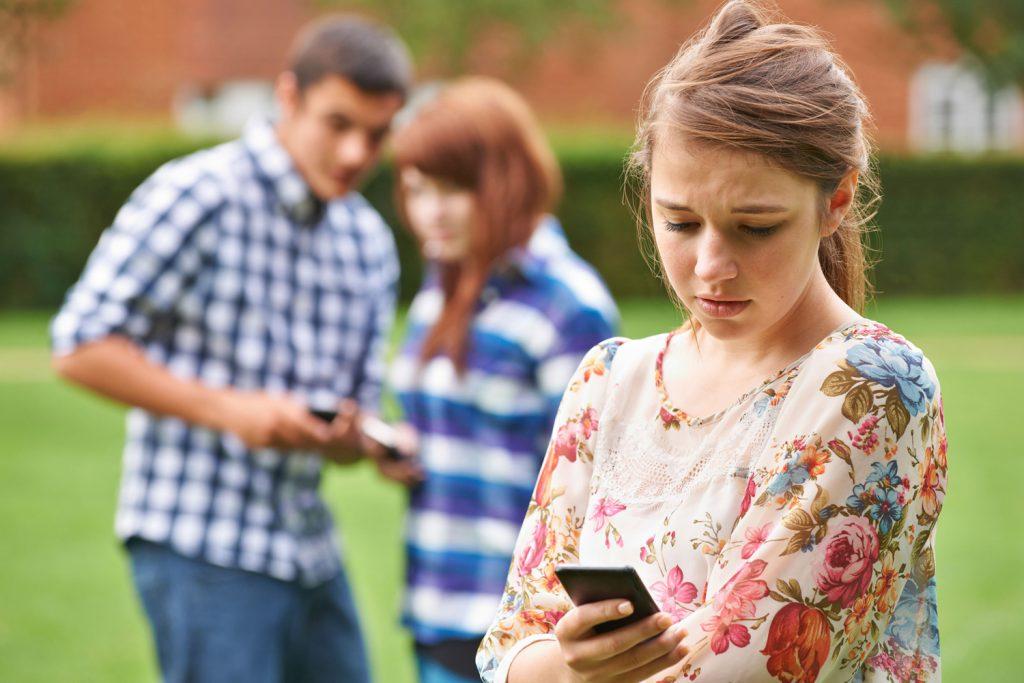 Mädchen mit Handy, im Hintergrund zwei Jugendliche