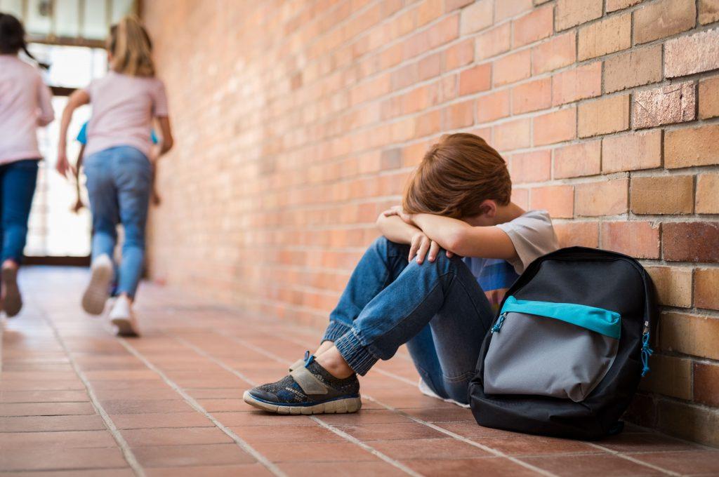 Schulkind sitzt am Boden