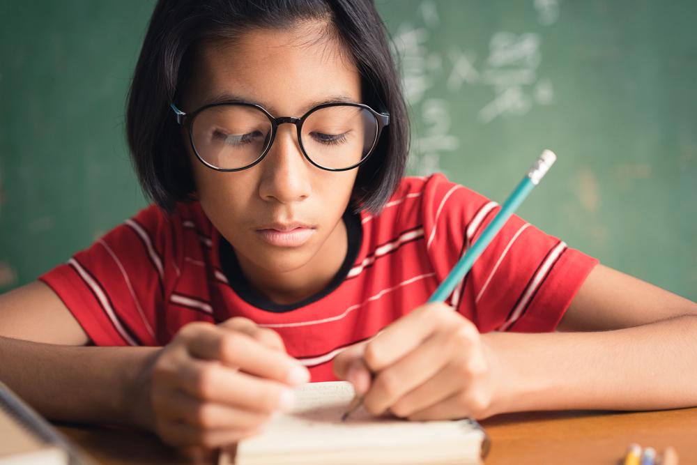 Schülerin sitzt am Schreibtsich und schreibt