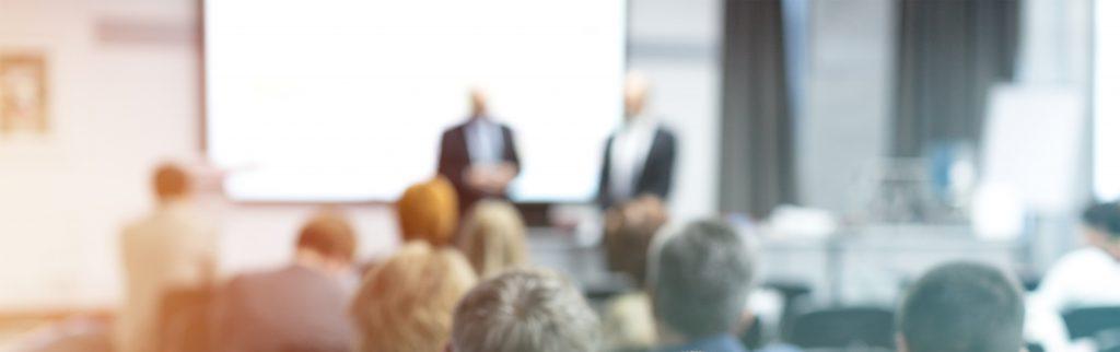 Zwei Männer in dunklen Anzügen halten einen Vortrag