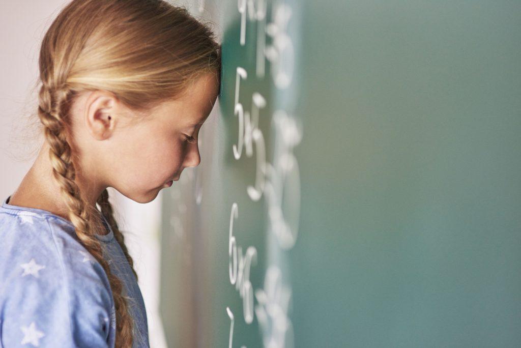 Schülerin lehnt mit Stirn an Wand